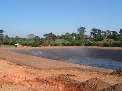 Topsoil being replaced around top and sides of reservoir