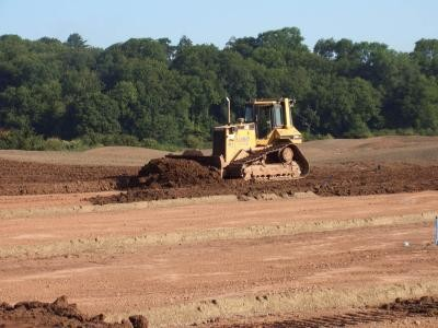 Dozer spreading topsoil between fairway drainage lines