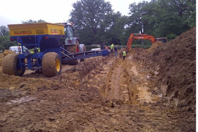 Deep drainage being installed through area of running sand