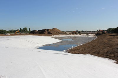 Topsoiling over lined embankments within the irrigation lake