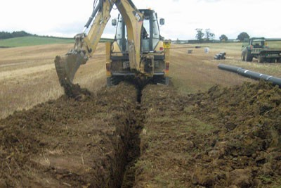 Installing carrier drain using excavator
