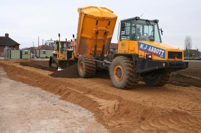 Dozer receiving topsoil for re-spread